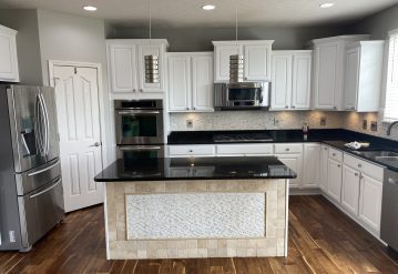 A closer look at the kitchen island with its white and beige colors and black countertop.