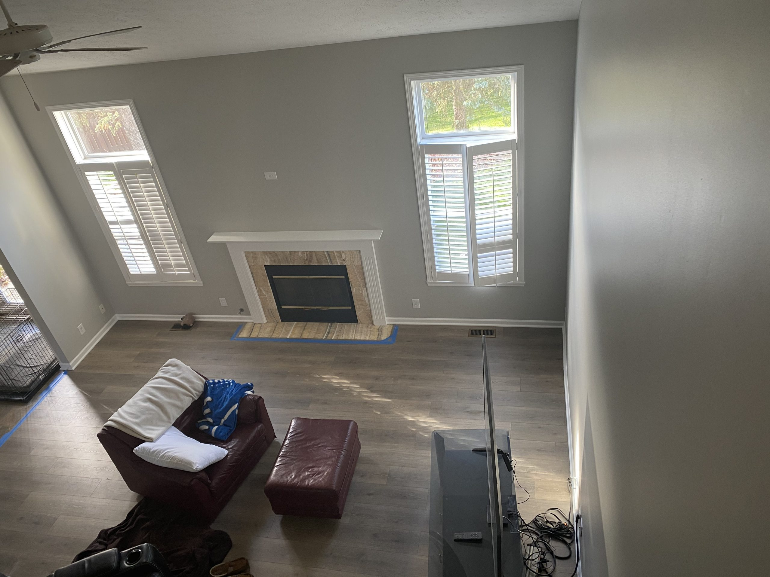 A picture from the second floor looking down on the living room showing the new gray walls and white trim around the fireplace.