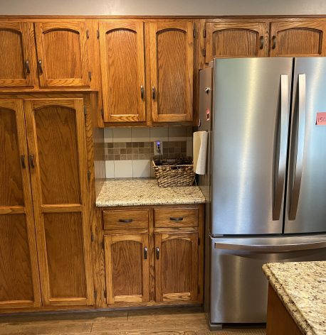 Wooden cabinets next to stainless steel refrigerator before the paint job has begun.