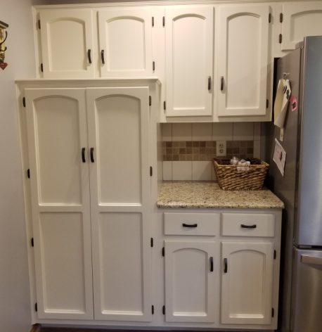 Freshly white cabinets next to a stainless steel refrigerator after the job is complete.