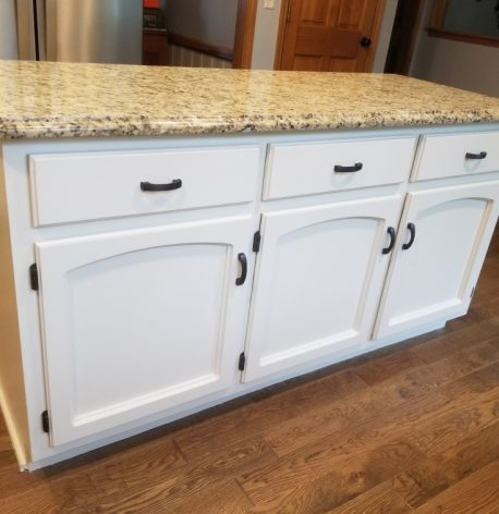 The kitchen island with newly painted white sides and cabinet doors.