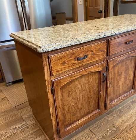 Kitchen island with wood cabinets before the job begins.