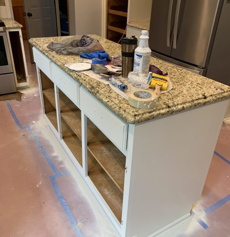 The island is a work in progress with fresh white pant and the cabinet doors removed.