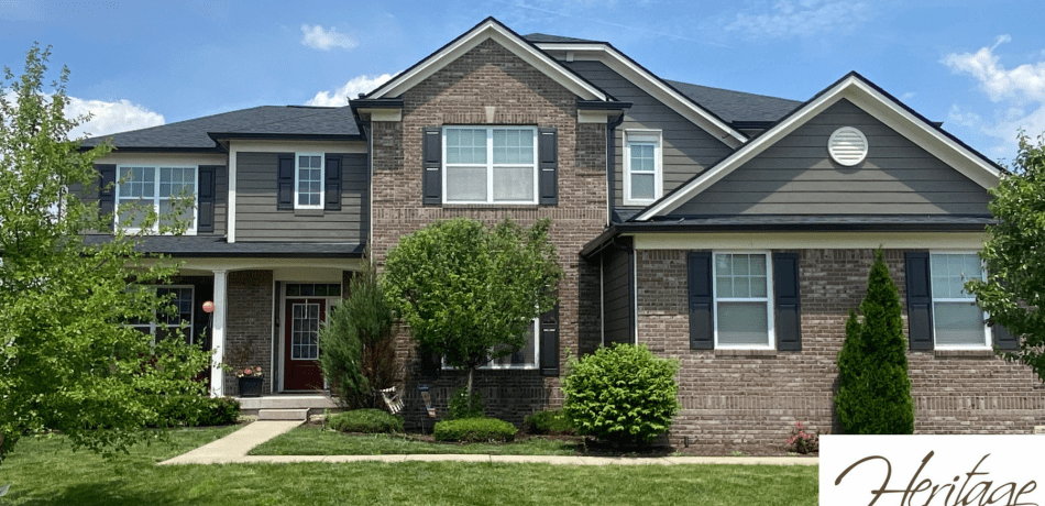 This house with a dark roof has dark siding, white trim and black gutters.