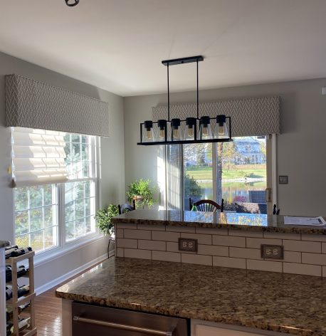 A modern kitchen interior with grey walls and a white ceiling.