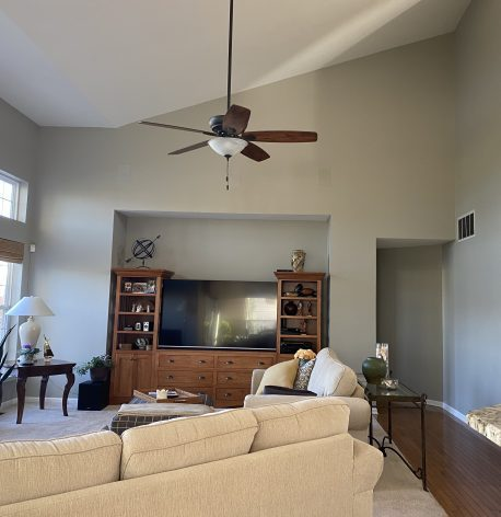 A living room with a high vaulted ceiling with grey walls and a white ceiling.