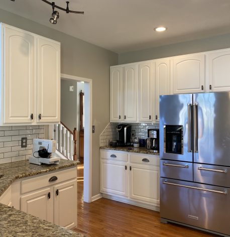 A modern kitchen with fresh white cabinets, grey walls, and a white ceiling.