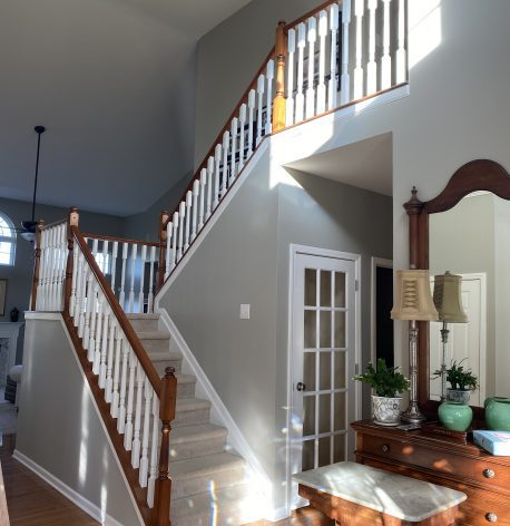 A staircase with freshly painted white trim, white banisters, and grey walls.