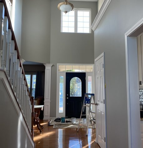 An interior shot of the front door showing new gray walls, white trim, and a white ceiling with a paint ladder and supplies still on the ground.