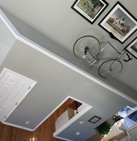 An angled shot of the downstairs showing the new gray walls, with a bicycle and some photos mounted on the wall.