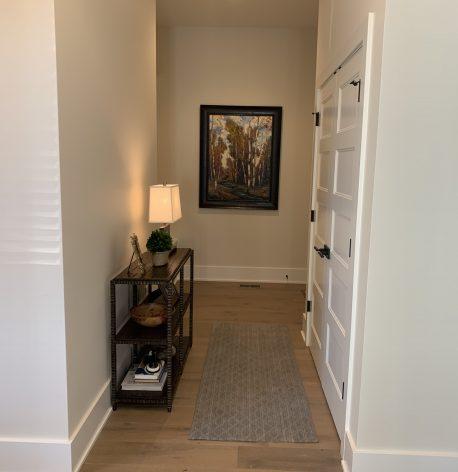 Hallway with satin white walls, semi-gloss white trim and wood floors