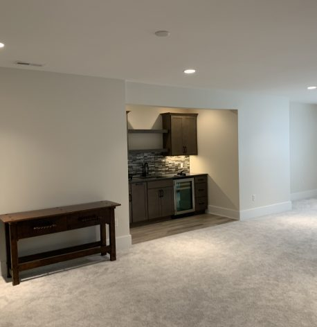 Spectacularly Painted Recreation Room with Satin White Walls and White Semi-Gloss Baseboards offset a Brown Wood Stained Built in Bar