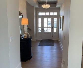 Beatufuly Painted entry way with satin white walls, white semi gloss doors, sidelights and baseboard trim. Wood Ceiling and Floors
