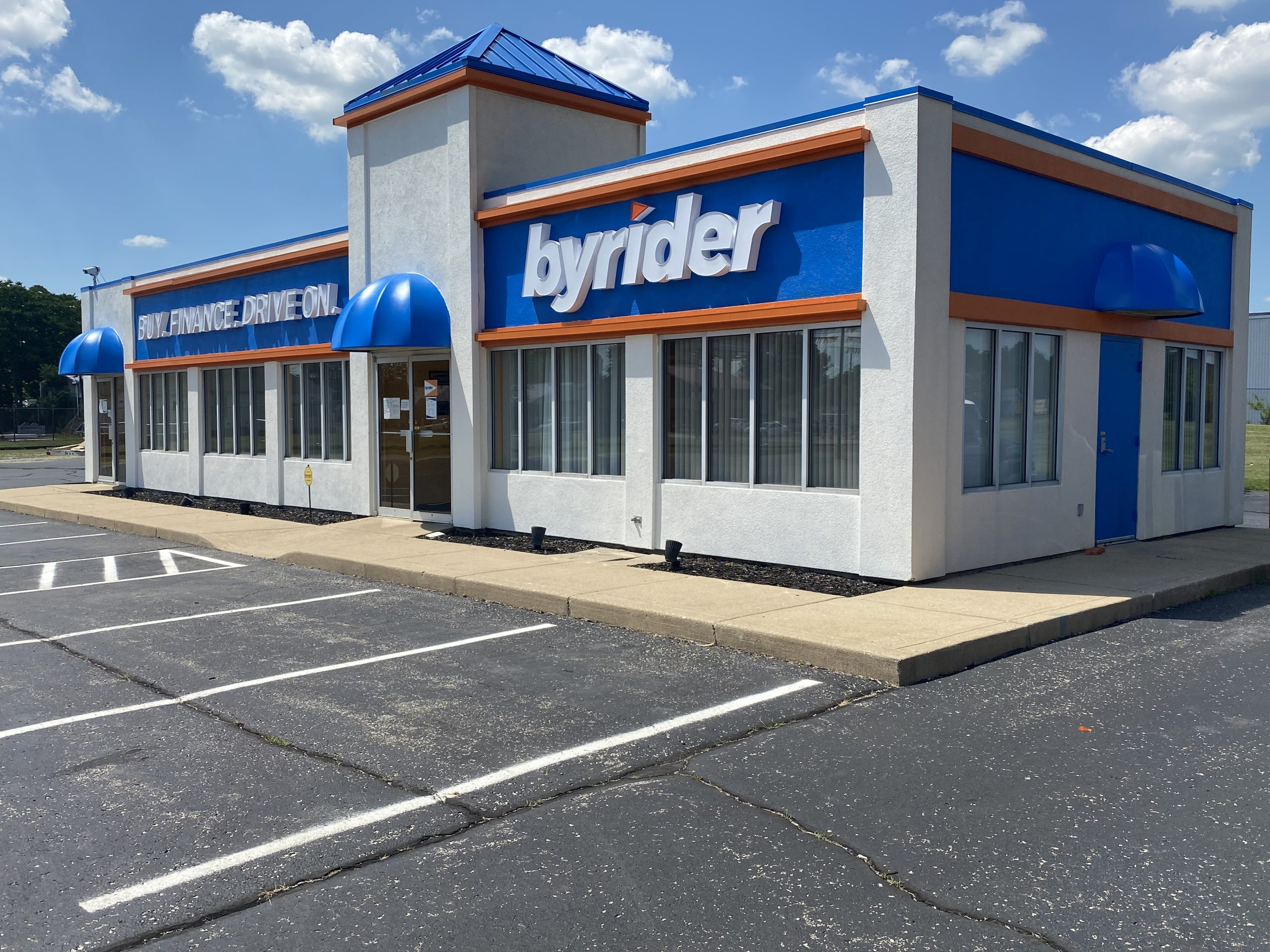 A freshly painted Byrider building showing the logo and orange and blue accents.