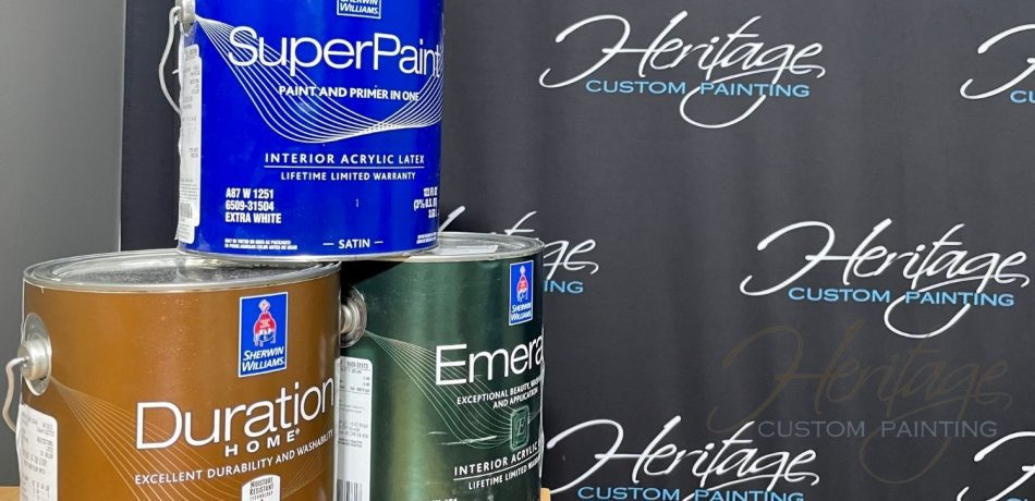 Three Sherman Williams paint cans stacked on a desk against a Heritage Custom Painting backdrop.