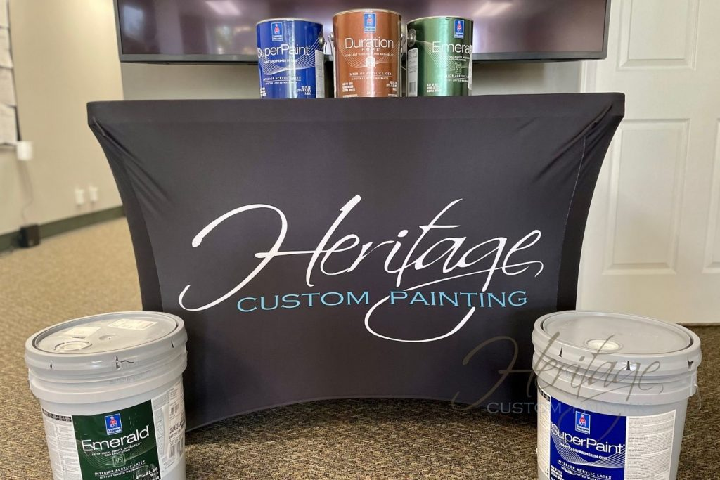 Three paint cans and two five gallon buckets set around a Heritage Custom Painting booth.