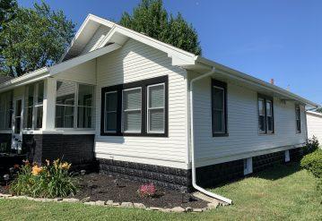 A newly transformed house with black trim around the windows to make them pop.