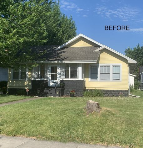 A before image of the house showing its yellow vinyl siding and white window trim.
