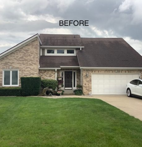 A before image of a house with a brick exterior with a garage.