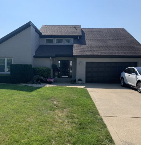An after image of the house showing its new grey exterior and dark accent on the garage door.