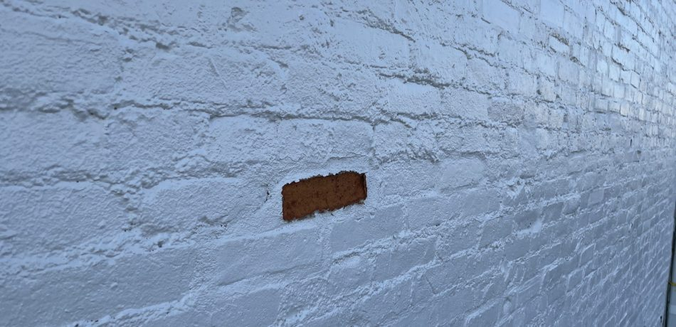 Painted brick after one has begun shaling.